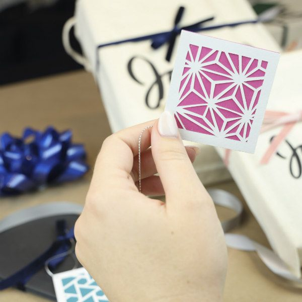 hand holding a geometric paper cut gift tag