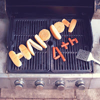 A steel barbecue grill with Happy 4th spelled out in buns and hotdogs.
