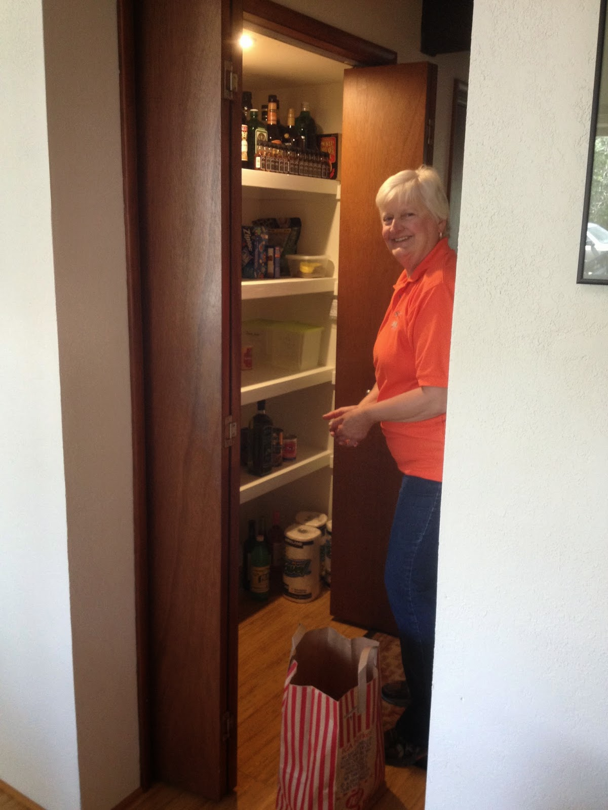Joan loads food from motorhome onto pantry shelves of our summer home