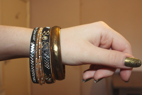golden green nails on a hand with bangles in black and gold