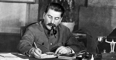 Famosa foto di Stalin che lavora seduto alla scrivania e fuma la pipa.