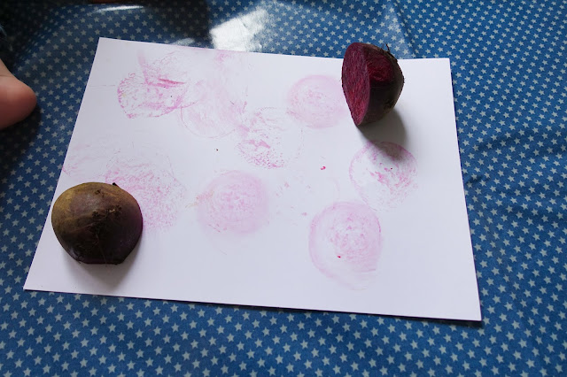 A white piece of card with 2 cut pieces of beetroot on placed on top of an oil cloth mat in blue with small white stars.
