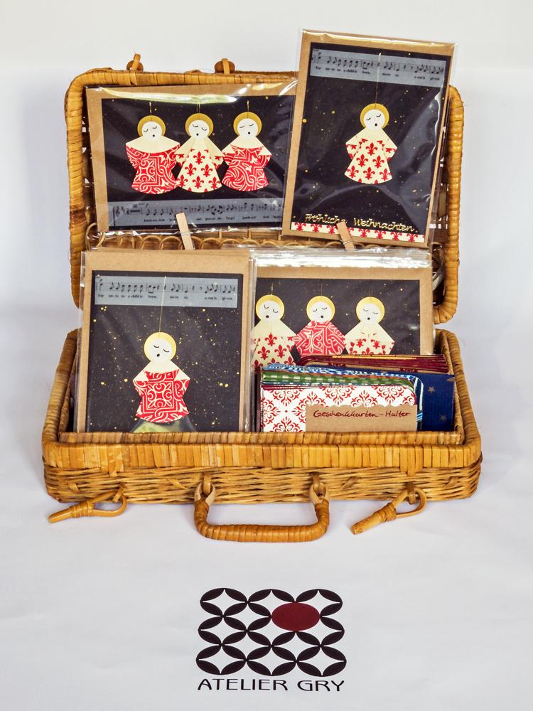 Karten mit singenden Engeln in einem Rattankoffer ausgestellt