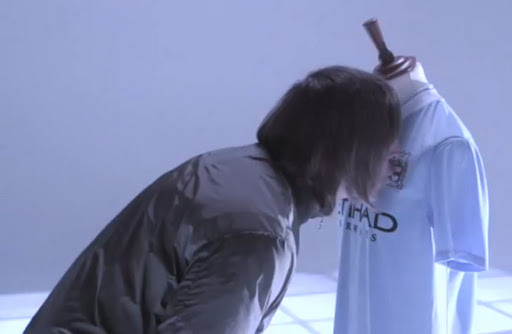 Liam Gallagher kisses the badge on new Manchester City shirt