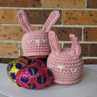 Five colourful easter eggs with a crochet bunny sitting on top, and a second bunny to the right. The crochet bunnies are the same, made with a muted rose pink cotton yarn with cream embroidered sleepy eyes and nose.