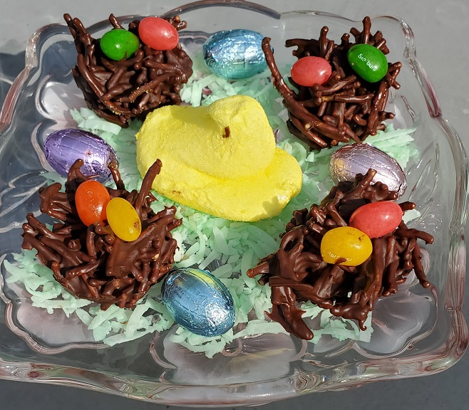 these are haystacks with chocolate and Asian noodles on a lenox plate with some tinted coconut, peeps and jelly beans