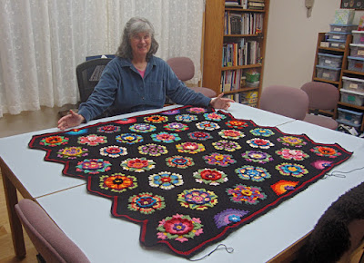 Robin Atkins with nearly completed crocheted afghan, Frida's Flowers