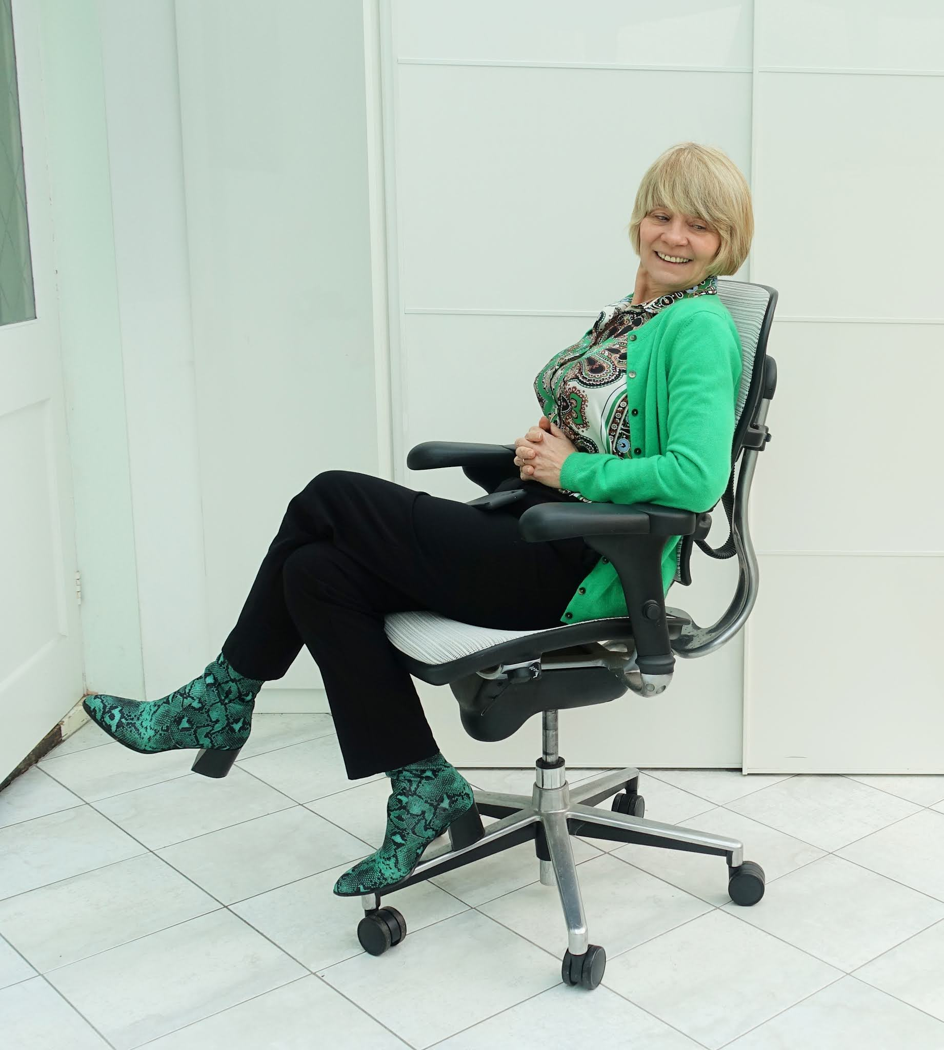 Wearing your normal work clothes makes a huge difference to how you feel about working from home.  Is This Mutton's Gail Hanlon in black trousers, paisley blouse and cashmere cardigan with green snakeskin boots