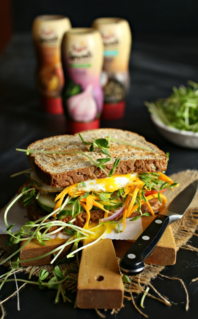 Recipe for a sandwich, dressed with hummus and filled with avocado, tomato, cucumber, carrots and a fried egg.
