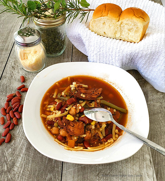 This is a white soup dish with minestrone soup in it along with grated cheese in the background, oregano in a mason jar, sprigs of rosemary and large yeast rolls in a wicker basket there are also red kidney beans that are raw on the wooden grey table