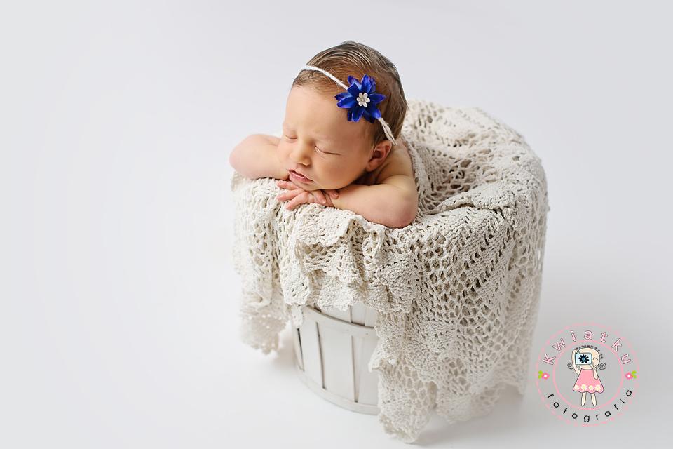 Zdjęcie dziecka w wiaderku z niebieskim kwiatkiem