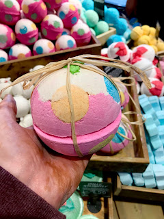 A bright massive purple bath bomb with light brown rope in the middle with a white top with green holly decorated on top with big spots of different colours on the side with other spherical bath bombs in the background on a bright background