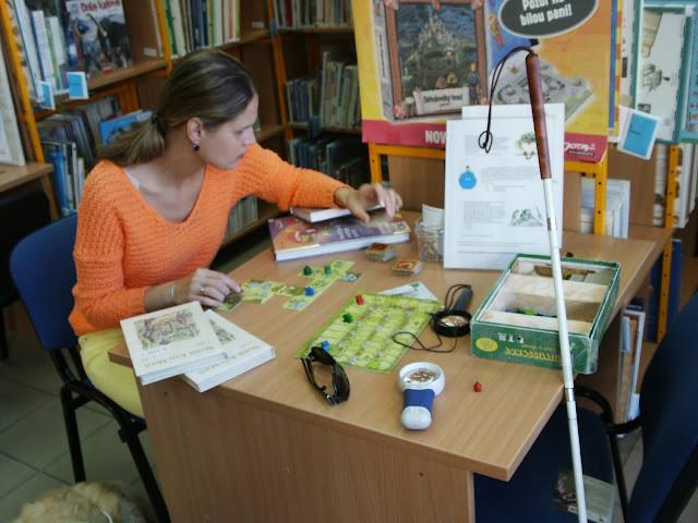 Linda v knihovně u stolu. Na stole rozehraná hra Carcassonne a knihy