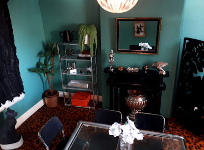 One-twelfth scale modern miniature art-deco inspired dining room with leopard-print carpet and chrome table, chairs and book shelf.
