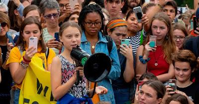 No final das contas, Greta Thunberg e outros autistas envolvidos na luta ambientalista também estão defendendo o bem-estar e a inclusão dos autistas, mesmo que indiretamente. (Foto: Alastair Pike/AFP/Getty Images) Descrição da imagem #PraCegoVer: Greta Thunberg, uma adolescente branca de cabelos presos e blusa colorida sem mangas, discursa em um megafone, em meio a vários manifestantes segurando celulares para tirar fotos, numa manifestação contra o descaso dos governos perante a crise climática global. Fim da descrição.