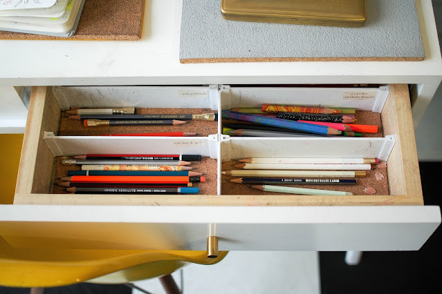 A battered desk with the drawer open, containing sections with different pencils in