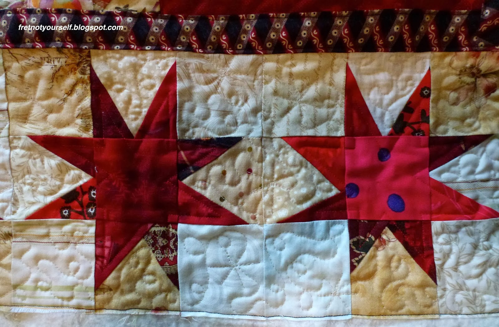 Free motion quilting starlights and loops in the border complements the variable stars.
