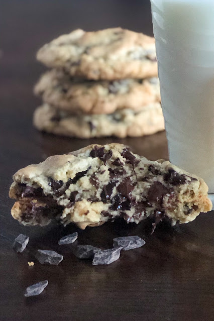 large chocolate chip cookie from the inside with a glass of milk