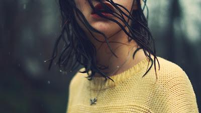 Chica con pelo mojado un blusa amarilla por la calle