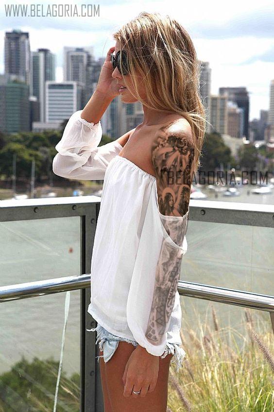 Mujer rubia en un balcon frente a la ciudad, lleva el tatuaje de un angel en el brazo