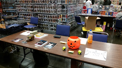 A vendor table at a comic book convention with two stacks of books, a fake skull and a Jack 'O Lantern candy bucket.