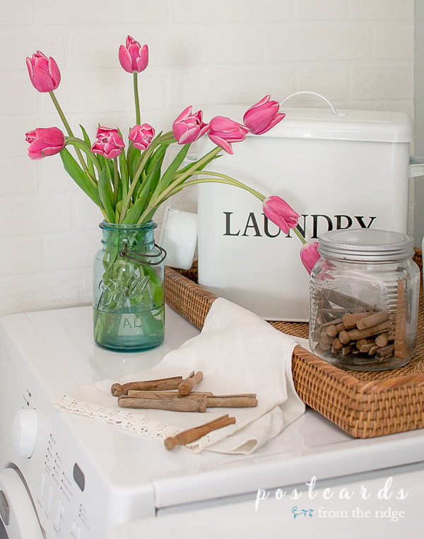 pink tulips in a vintage blue mason jar on a dryer, vintage wooden clothespins in glass jar