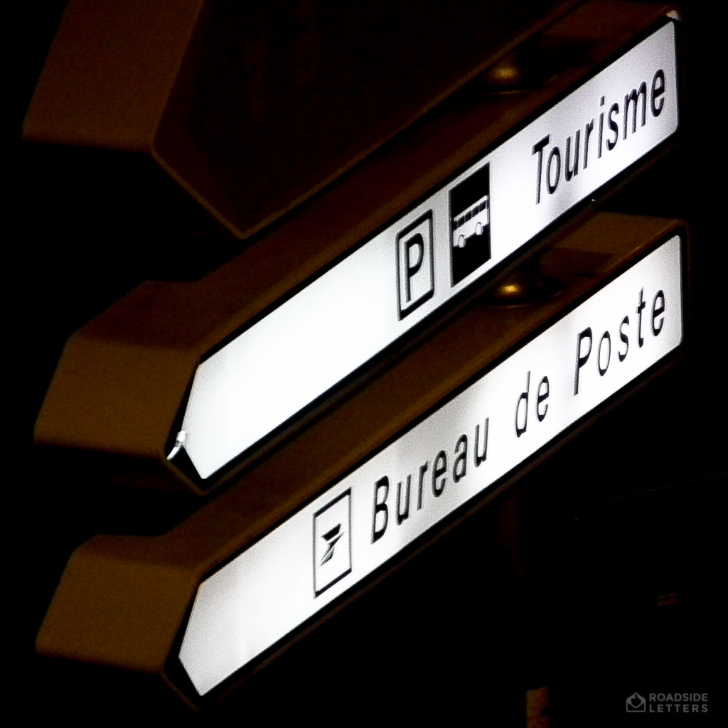 Lit street sign in France directing towards Post Office