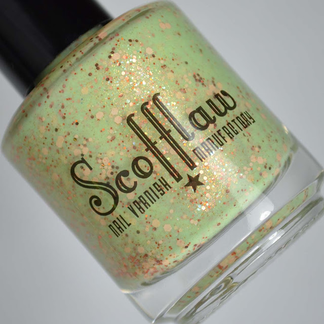green nail polish with warm toned glitters in a bottle