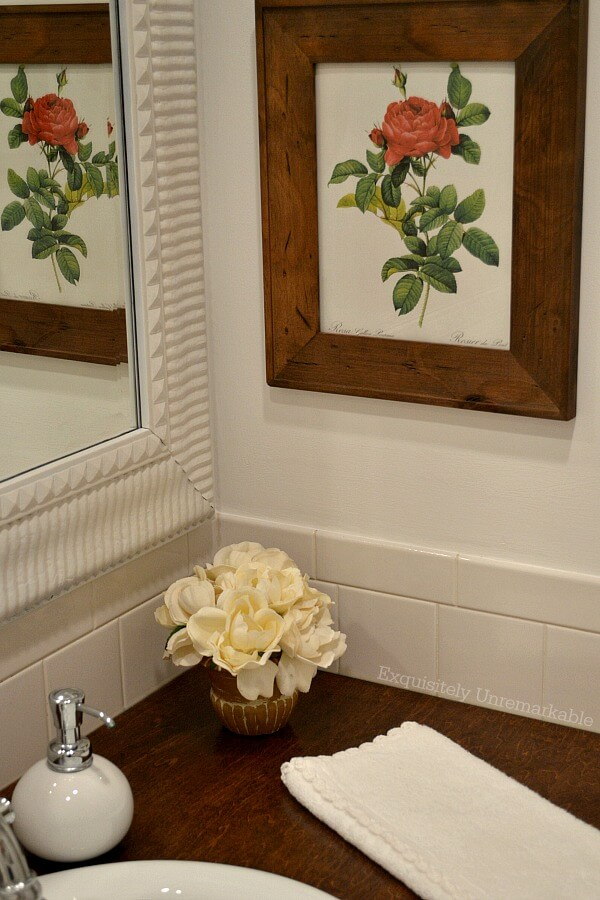 Red rose print framed on wall in bathroom with flower pot on wooden vanity top