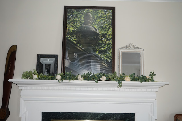 Mantel decorated with rose garland, chippy paint mirror, large urn picture