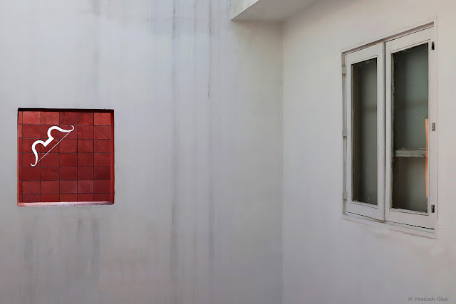 A Minimal Art Photograph of a White Bow on a Red Wall (Square) at Jawahar Kala Kendra, Jaipur.