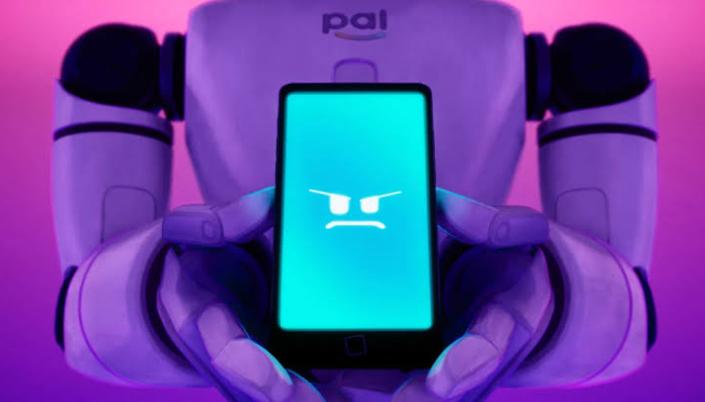 Descrição de imagem: Na imagem vemos um robô branco segurando um celular. Na tela do celular vemos um rosto digital feito de de caracteres, o rosto é da vilã PAL, a qual está tem um semblante ameaçador.