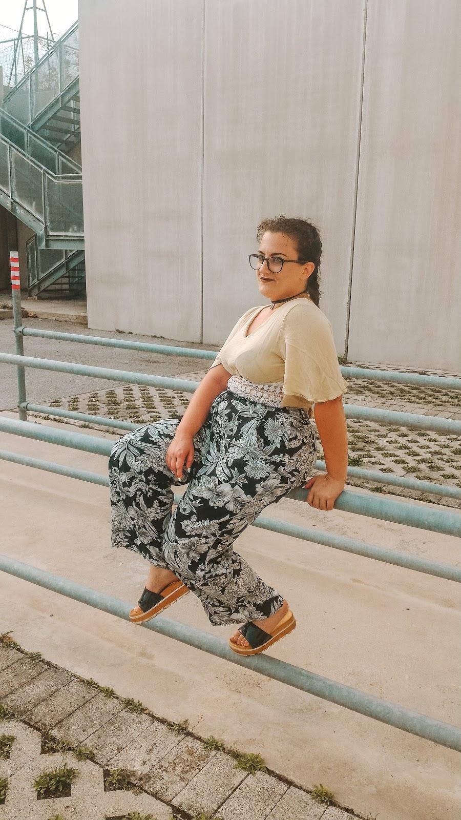 ragazza seduta che indossa un crop top giallo e dei pantaloni floreali