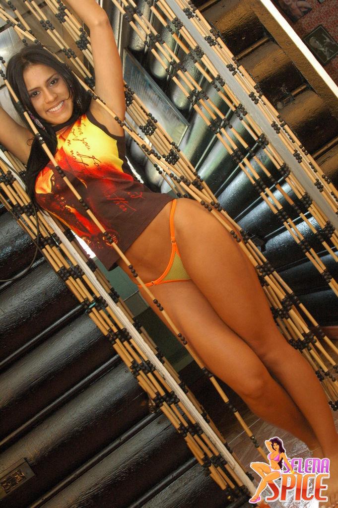Andrea Rincon, Selena Spice Galeria 36 : Shakiras, Camiseta Negra Con Amarillo y Rojo, Tanga Amarilla y Naranja Foto 1