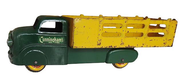 "Marx toy stake truck bearing ""Cunningham's Drug Store"" logo, with Marx metal wheels."