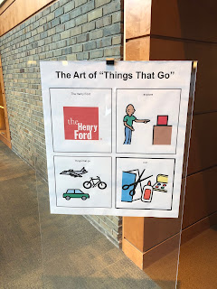 "Poster in stand with words at the top: The Art of ""Things That Go."" There are four squares with images inside: The Henry Ford logo, a person pointing to red box, images of 3 modes of transportation, and arts and crafts tools"