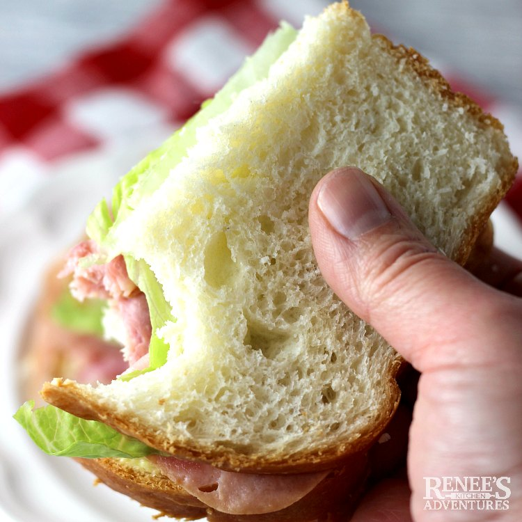 Half of a sandwich being held with a bite made from soft white bread