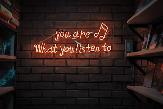 "Neon sign that reads ""You are what you listen to"""