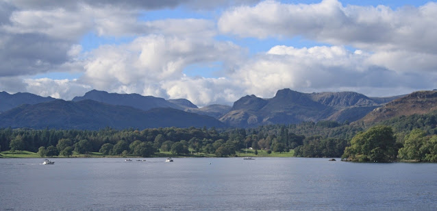 A view of boats on Lake Windermere, with hills in the background. It's a sunny day with some, scattered clouds.