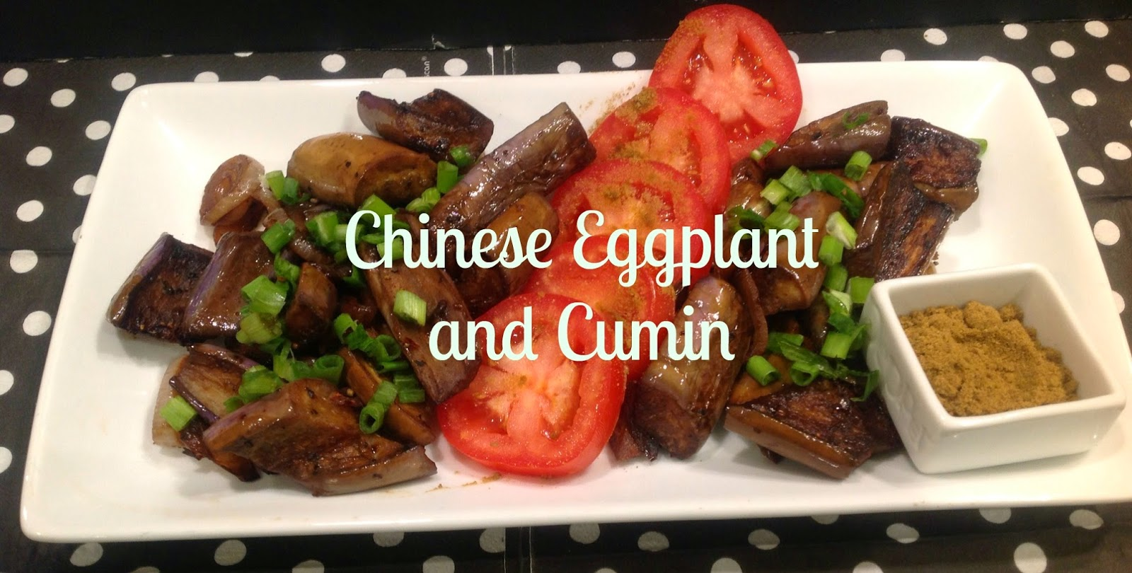 chinese eggplant, tomatoes, and green onion on a plate with a container of cumin