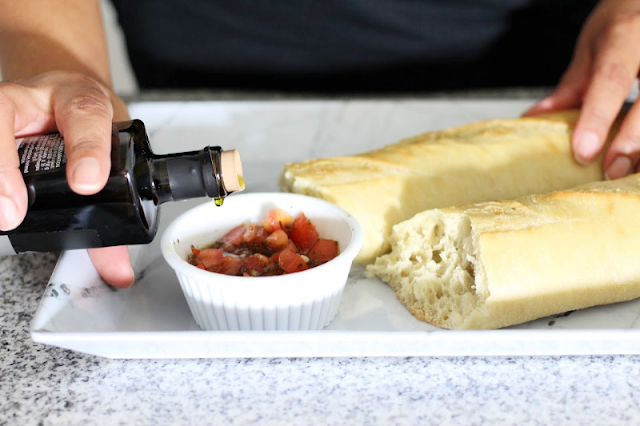 french bread and tomatoes with olive oil bottle on counter