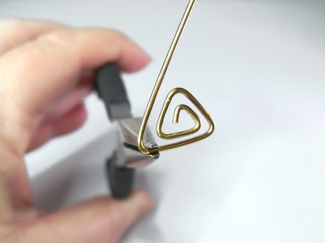 Using chain nose pliers to bend the wire at a 60° angle.