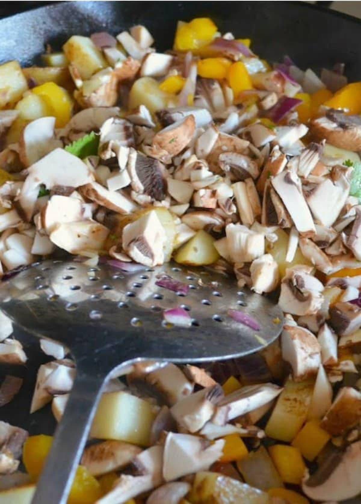 Add sliced mushrooms to breakfast potatoes for Breakfast Burrito Recipe.