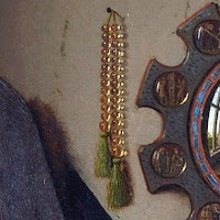 Prayer beads, which is found in three monotheistic religions, symbolize religious background for Giovanni Arnolfini