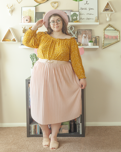 An outfit consisting of a pink wide brim hat, a mustard yellow microfloral off the shoulder blouse with frilly long sleeves, tucked into a pastel pink midi skirt with pastel pink slide sandals.
