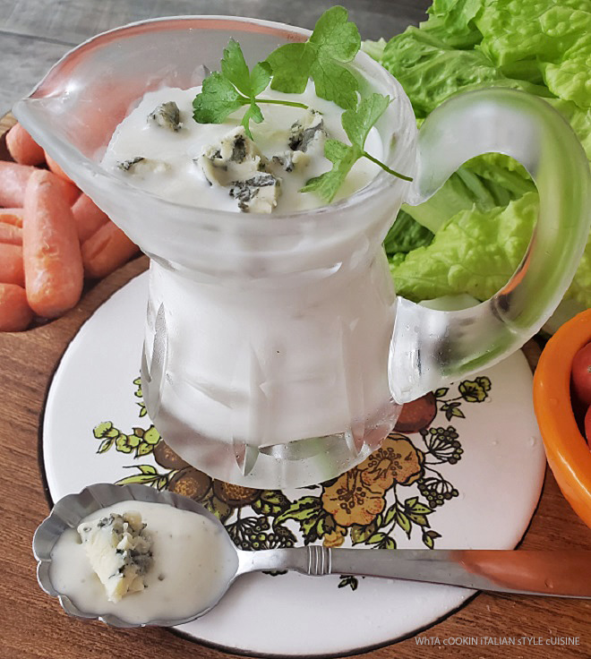 this is a pitcher made of glass filled with  homemade buttermilk blue cheese dressing with crumbles on top. It's on a cutting board with lettuce tomatoes and carrots for salad
