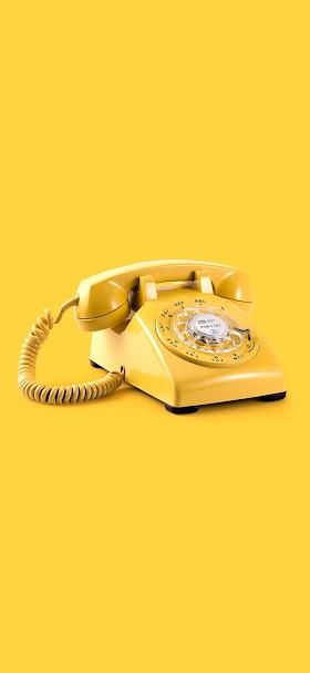 خلفية هاتف كلاسيكي قديم أصفر بخلفية صفراء
