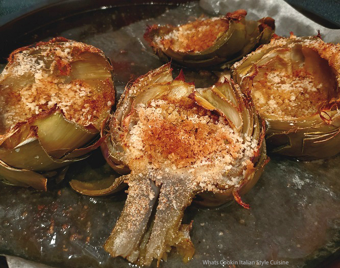 this is a pan of sliced in half artichokes stuffed with crab meat and bread crumbs