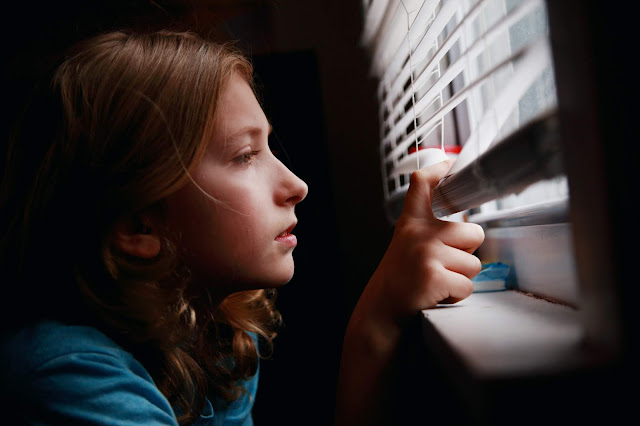 A young girl looking outside the blinds of her window
