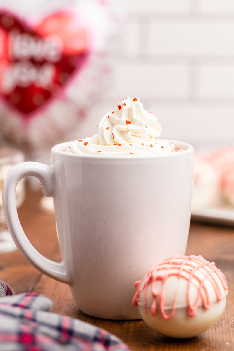 Closeup photo of a white mug full of hot chocolate made with Keto Valentine Hot Chocolate Bombs and topped with whipped cream and red edible glitter with a Keto Valentine Hot Chocolate Bombs sitting on the table next o the mug.